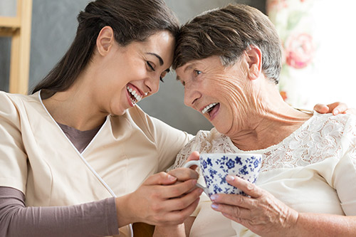 Image of a staff member and a resident enjoying a cup of tea.